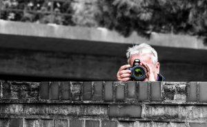 Fotografierender Mann hinter einer Mauer